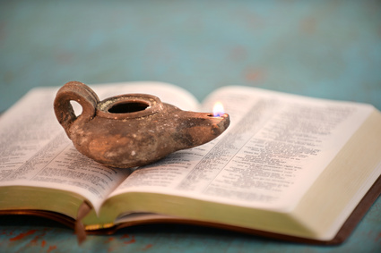 Ancient Oil Lamp on Open Bible