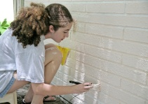 A teen girl painting house trim. Room for text.